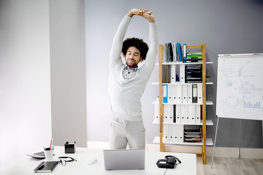 Man standing and stretching in the office