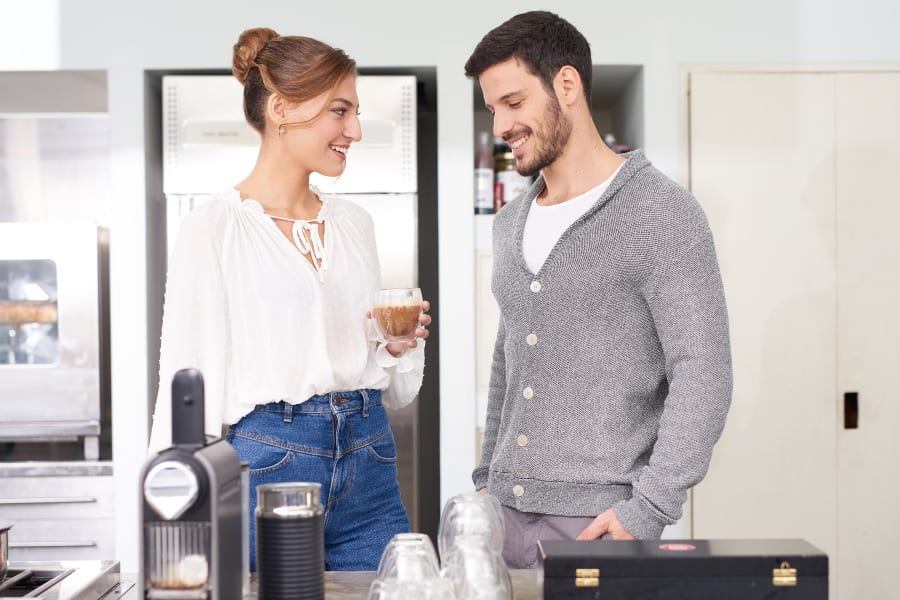 Woman with impressive posture standing in kitchen with man