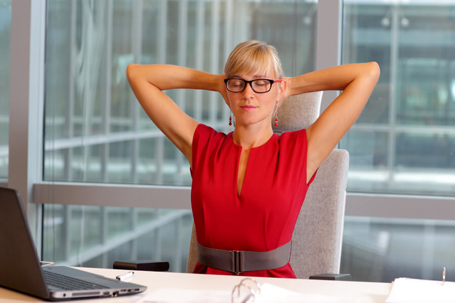 Woman doing thoracic extensions at her desk.