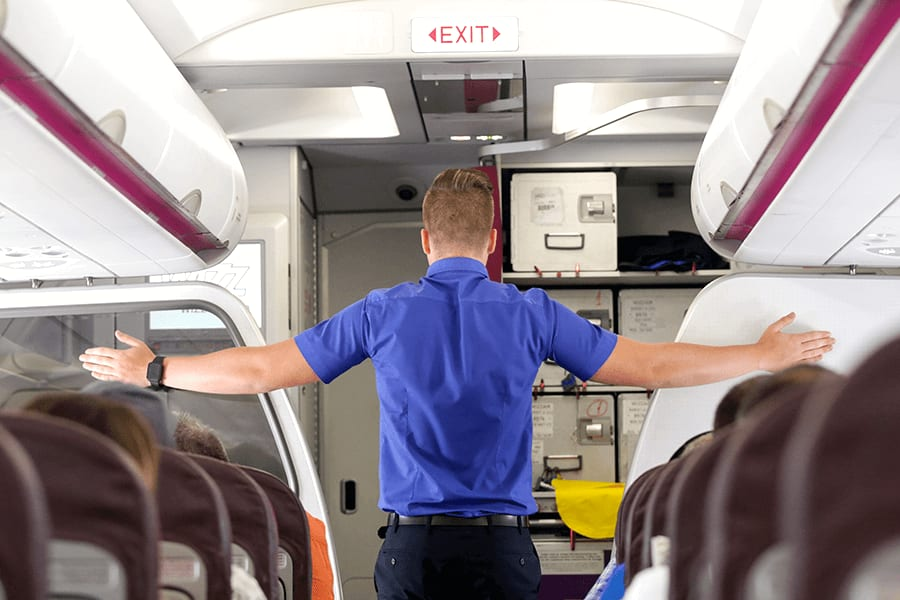 Male flight attendant pointing to emergency exits with both hands.