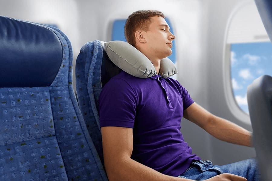Sleeping male passenger with neck pillow, demonstrating correct travel posture.