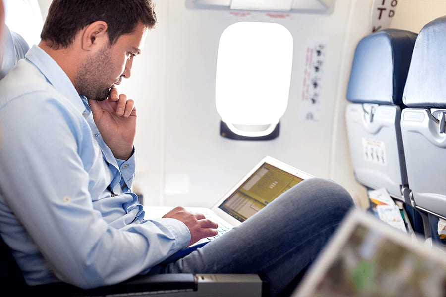 Male passenger looking at a laptop on his lap, demonstrating poor travel posture.