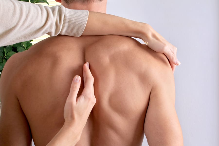 Man being checked for rounded shoulders by a doctor.