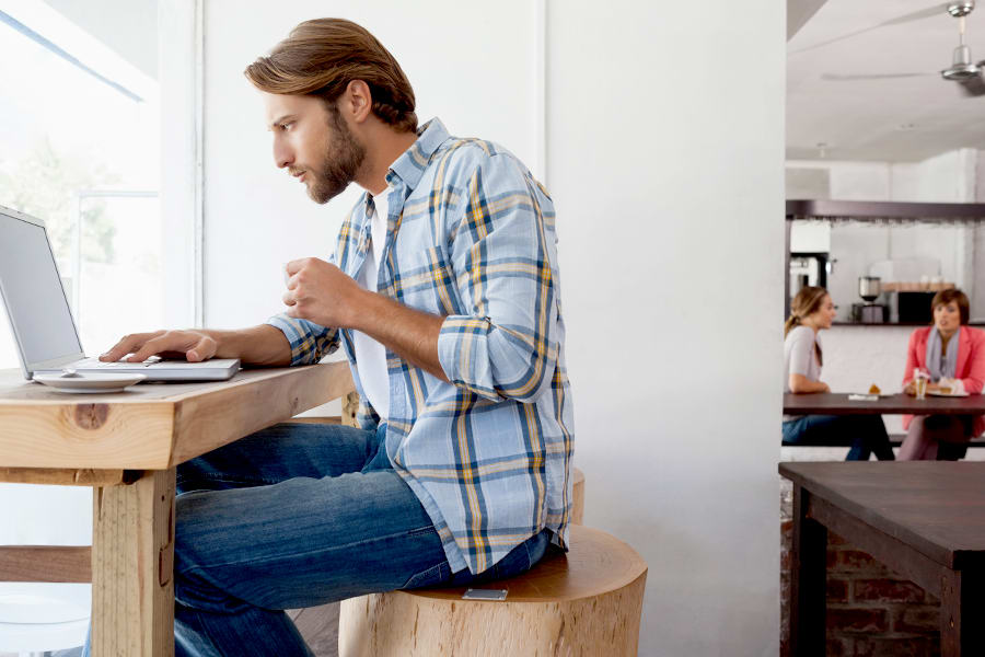 Man hunched over his laptop.