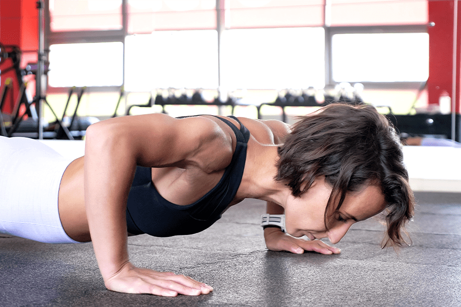 Woman doing push-ups in the gym to prevent rounded shoulders.