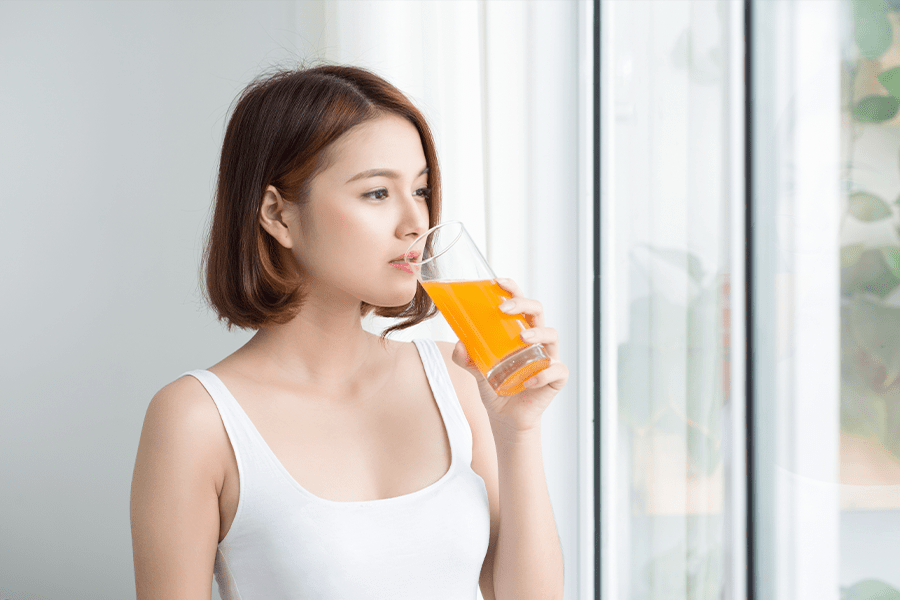 Woman drinking orange juice for strong, healthy muscles.