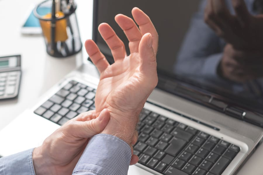 Office worker with Carpal Tunnel Syndrome holding wrist in pain
