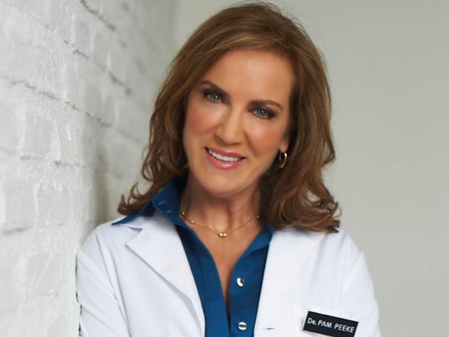 Dr. Pam Peeke leaning against a wall and smiling