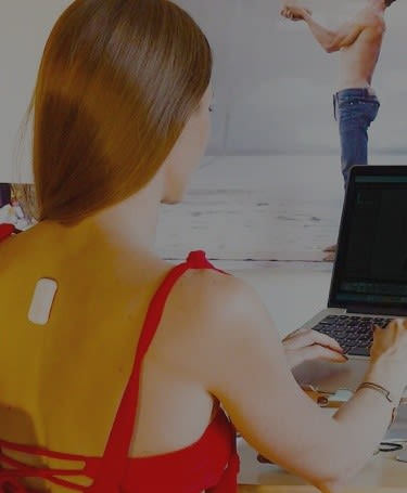 Woman working at her desk with Upright device on her upper back