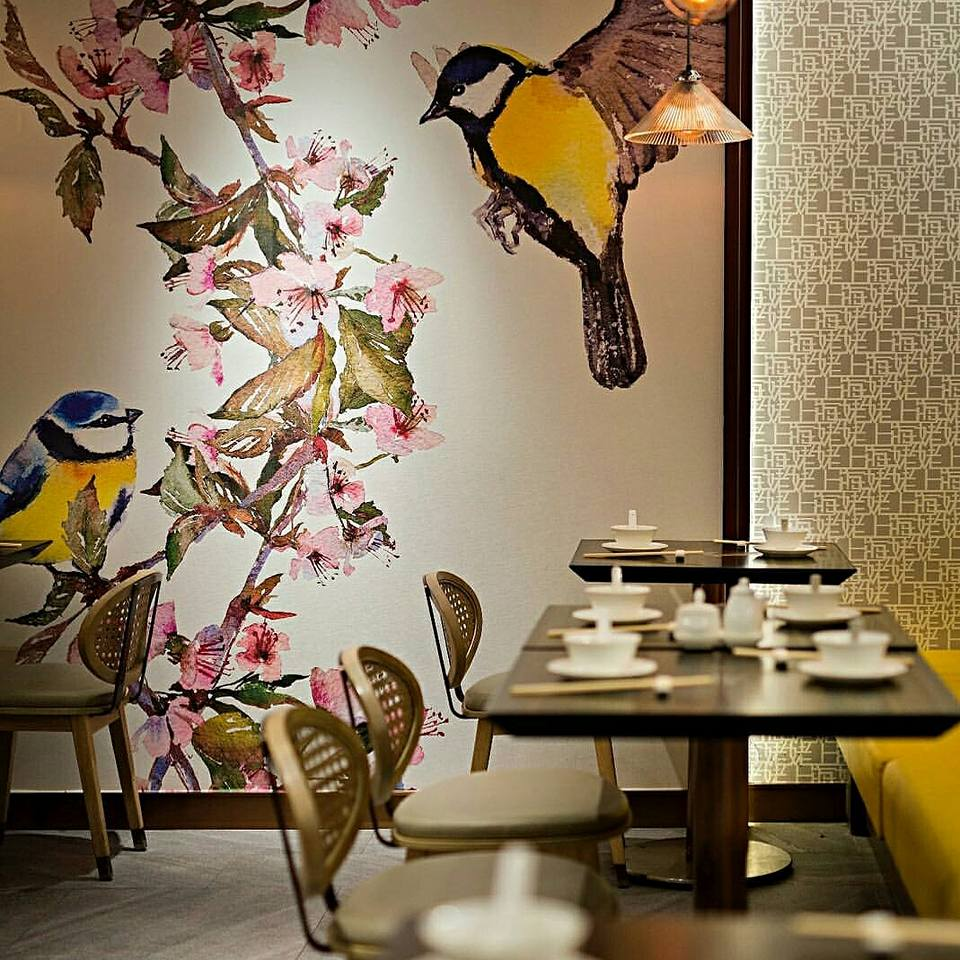 Restaurant With Wooden Table And Cushioned Chairs And Vibrant Wall Art by Nishtha Nayyar Modern | Interior Design Photos & Ideas
