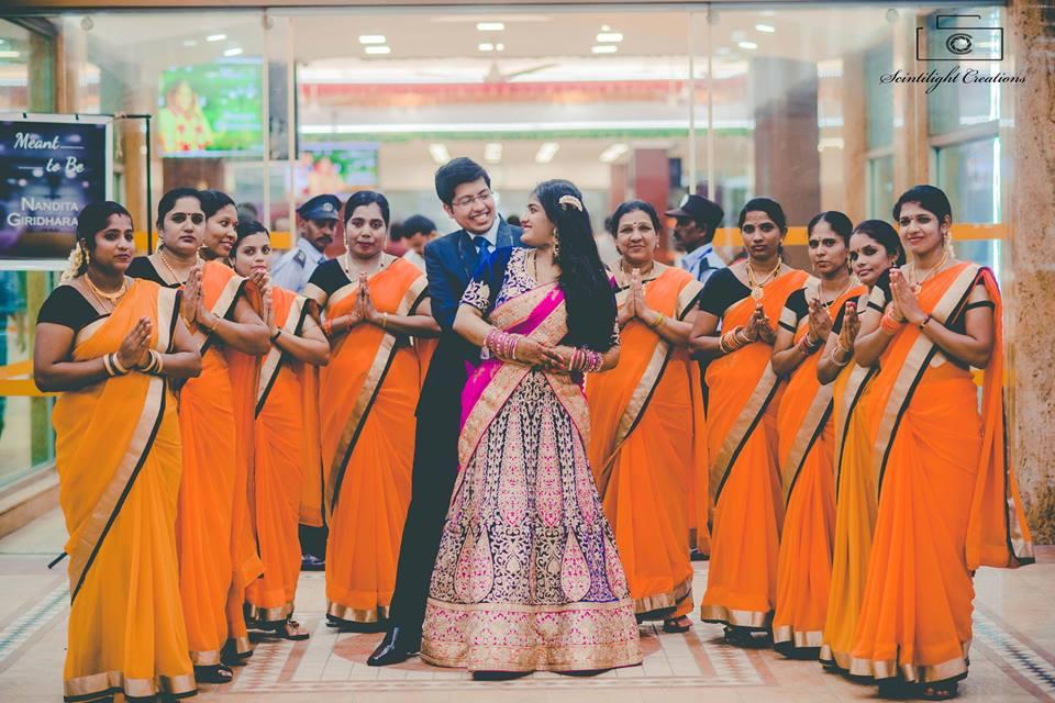 Bride and Groom Posing With Bridesmaid Wearing Orange Sarees by Gracian Wedding-photography | Weddings Photos & Ideas