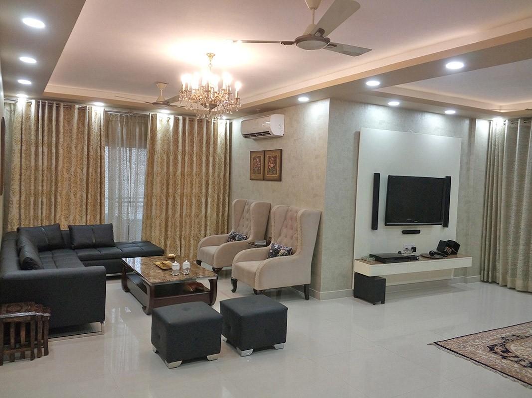 Spacious Living Room with Black L Shape Sofa Set and Beige Morgan Chairs by Ar. Barkha Jain Living-room Modern | Interior Design Photos & Ideas