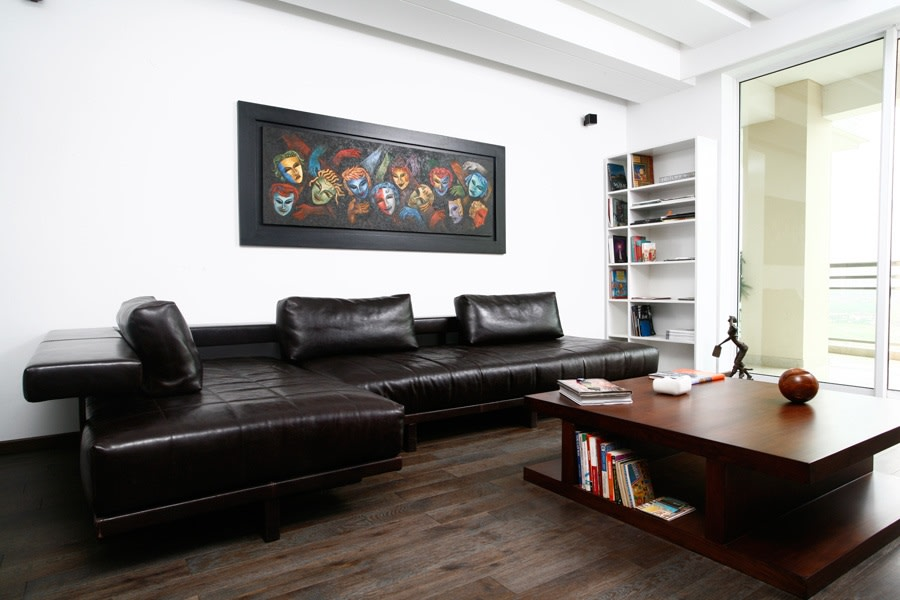 Black Sectional Sofa And Brown Wooden Table by Yogesh Goel Living-room | Interior Design Photos & Ideas