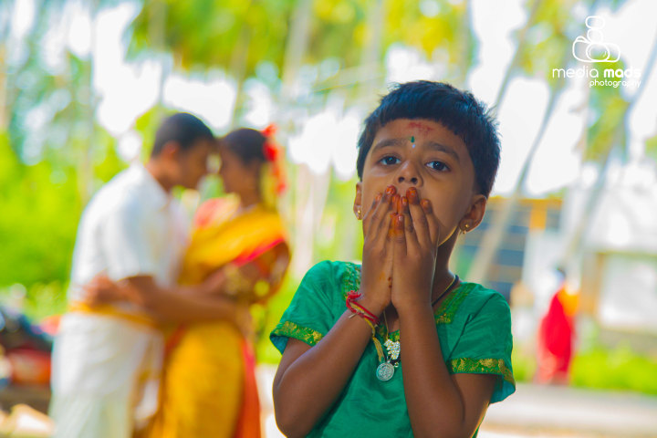 Stunning portrait of an innocent kid with the happy couple in background by Media Mads Wedding-photography | Weddings Photos & Ideas