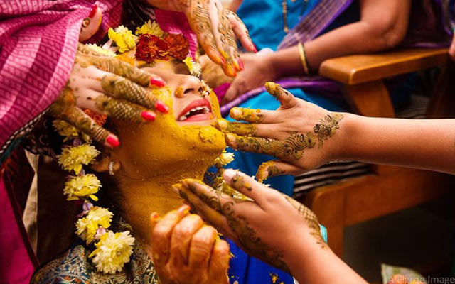 Vibrant Yellow Haldi being put on the bride's face by Flgroe Studios Wedding-photography | Weddings Photos & Ideas