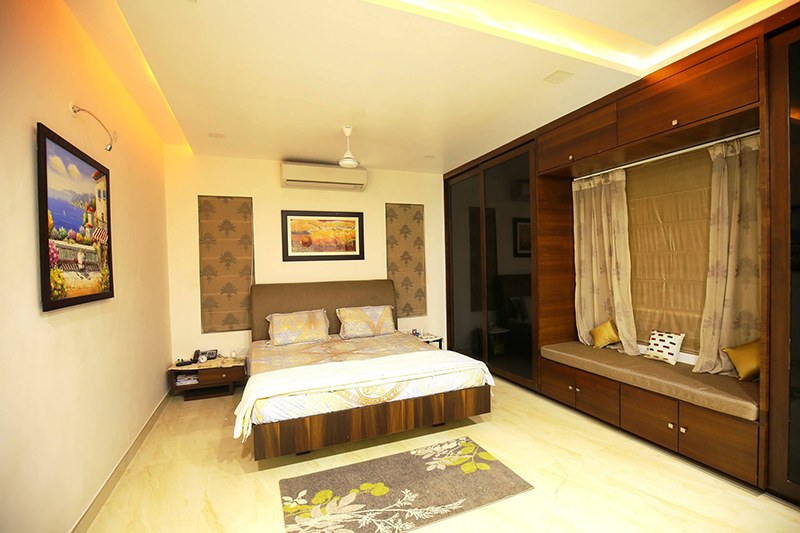 Low Rise Bed With Dark Walnut Wooden Wardrobe by Kraftworks Pvt. Ltd. Bedroom | Interior Design Photos & Ideas