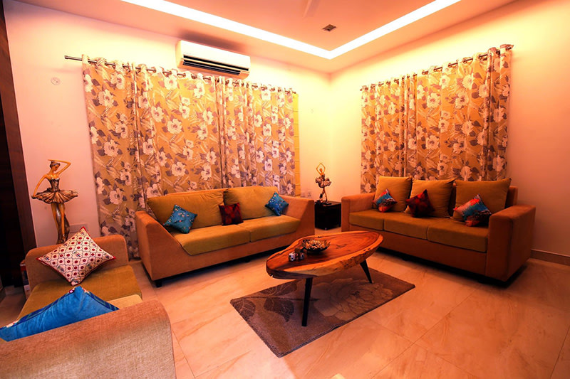 Mustard And Brown Lawson Sofas And Wooden Table by Kraftworks Pvt. Ltd. Living-room | Interior Design Photos & Ideas