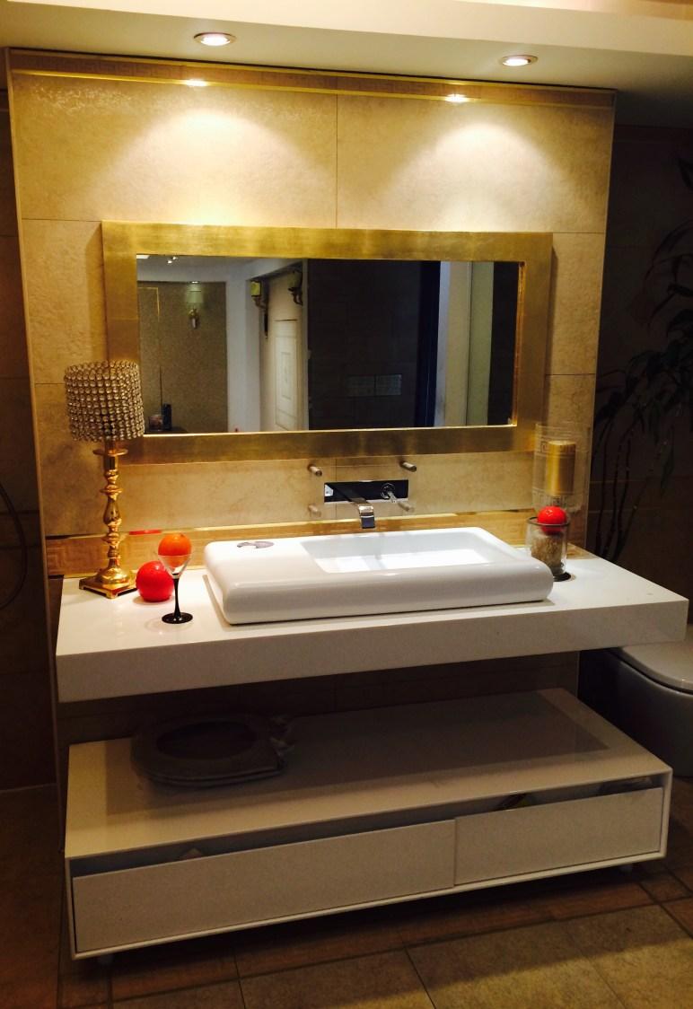 Golden Theme Bathroom With White Sanitaryware by Sakshi Gugnani Bathroom Modern | Interior Design Photos & Ideas