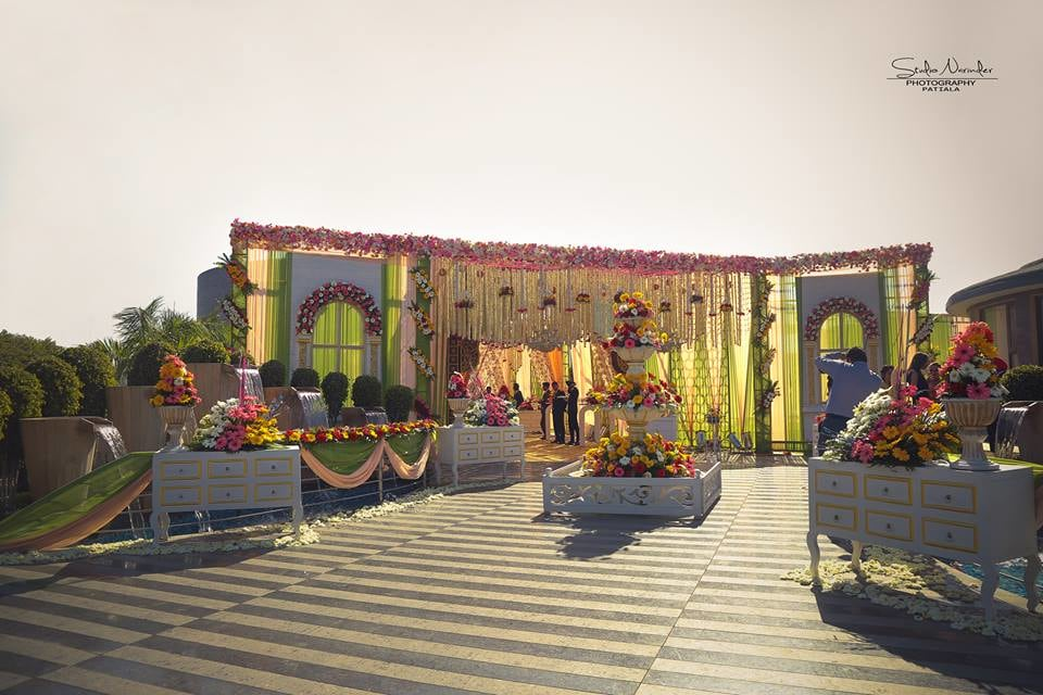Floral Entrance Decoration With Vibrant Flowers Mounted on Tiered Fountain And Dangling On Entrance Gate by Sourab Sharma Wedding-decor | Weddings Photos & Ideas