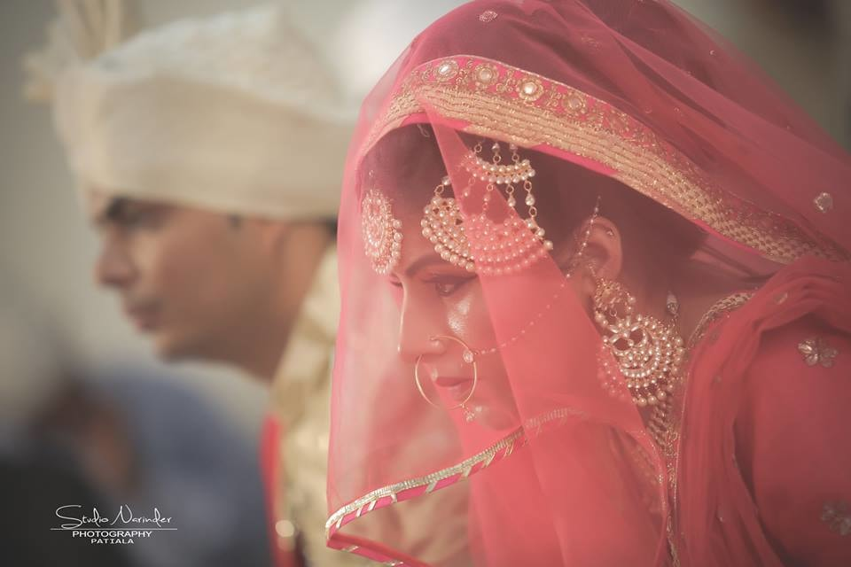 Candid Shot Of Bride Under Pink Net Veil Highlighting Her Crescent Kundan Side Mang Tikka And And Earrings by Sourab Sharma Wedding-photography | Weddings Photos & Ideas