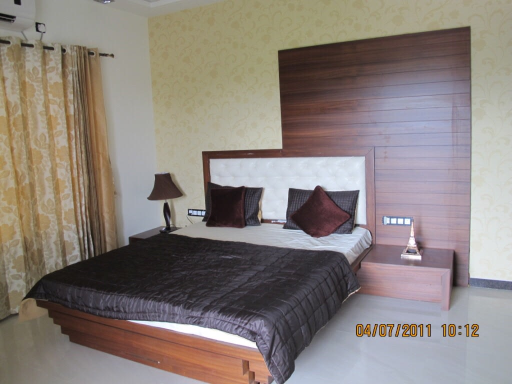 Bedroom With Timber Wood Bed And Yellow Curtains by Kalyani Kulkarni Bedroom Contemporary   Interior Design Photos & Ideas