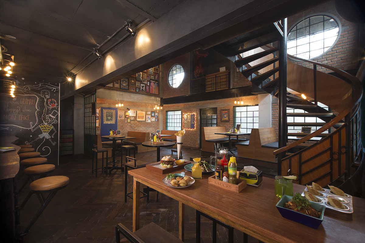 Restaurant With Twisted Staircase And Wooden Furniture by Jatin Hukkeri