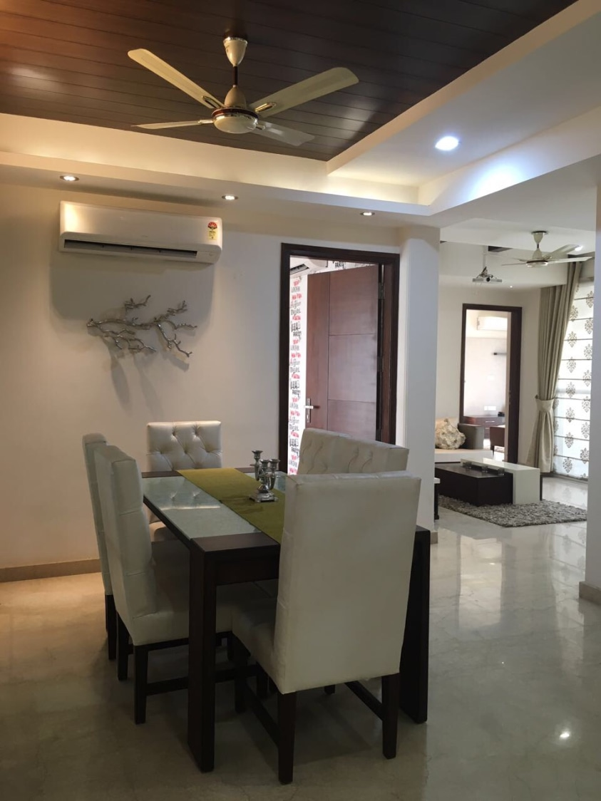 Regal Dining Room With White Leather Side Chairs and Glass Top Dining Table by Neha Chopra Dining-room Modern | Interior Design Photos & Ideas