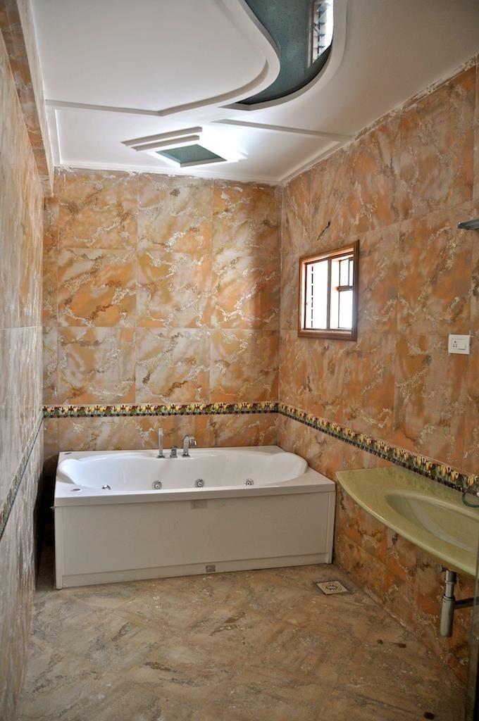 Bathroom with Patterned Tiles Walls and White Bathtub by Viraf Laskari  Bathroom Modern | Interior Design Photos & Ideas