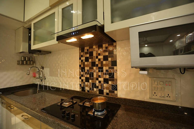 Parallel Modular Kitchen With Brown and Beige Mosiac Tiles and Brown Granite Slab by Innovations - The Interior Studio