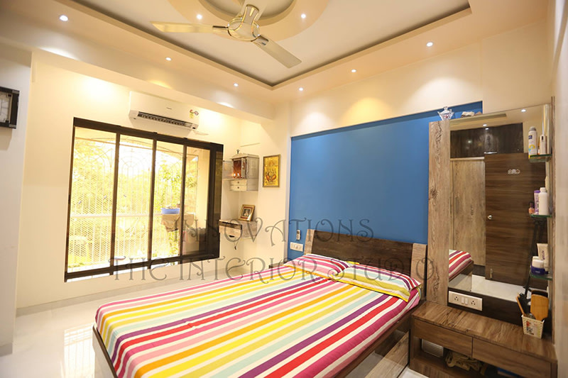 Bedroom With Cobalt Blue Wall and Wooden Low-Floor Bed by Innovations - The Interior Studio