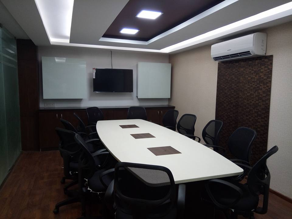 Meeting space with white table and black chairs around by Ganesh Contemporary | Interior Design Photos & Ideas