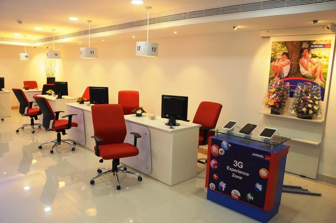open office space with red chairs and white table by Ganesh