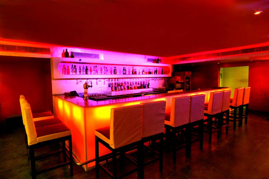 Classy Looking Bar with Red Lighting and White Chairs by Mayank Manchanda Modern | Interior Design Photos & Ideas