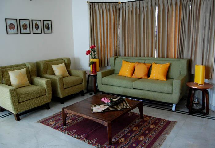 Wooden Sleek Table And Green Bulky Sofa In Living Room by Nishajyoti Sharma Living-room Contemporary | Interior Design Photos & Ideas