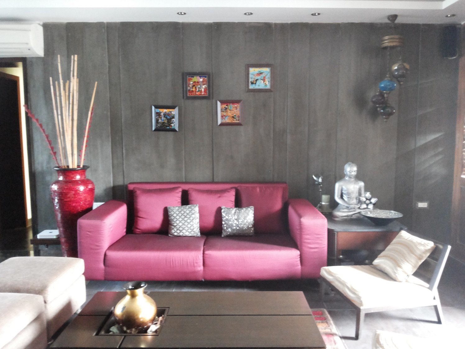 Living space with wooden wall decor and pink sofa by Milind Kapadia Living-room Modern | Interior Design Photos & Ideas