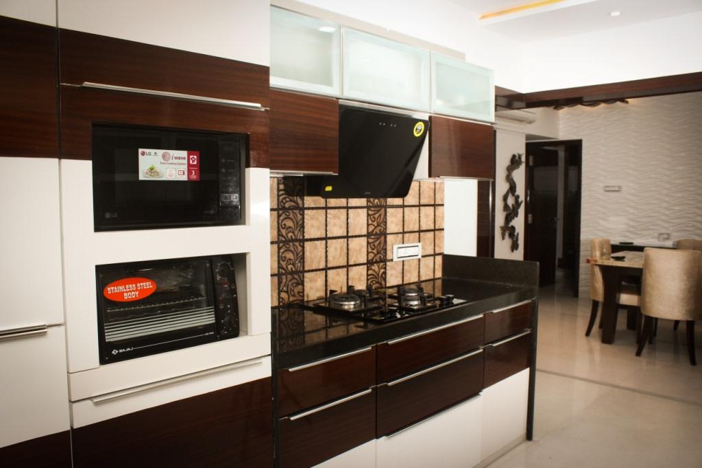 Wooden Cabinets In Modular Kitchen with black marble top by VERSATILE INTERIORS  Modular-kitchen Modern | Interior Design Photos & Ideas