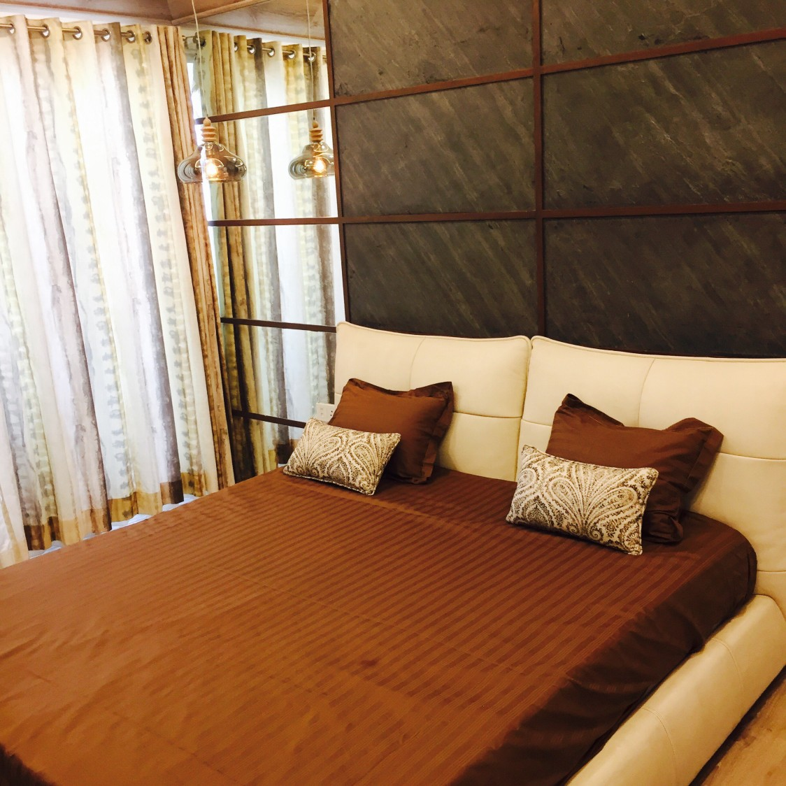 Brown and beige themed bedroom with a low rise bed and cushioned headboard illuminated by a hanging  designer lamp and natural light from curtain covered casement windows by Chaitanya Challa Bedroom Modern | Interior Design Photos & Ideas