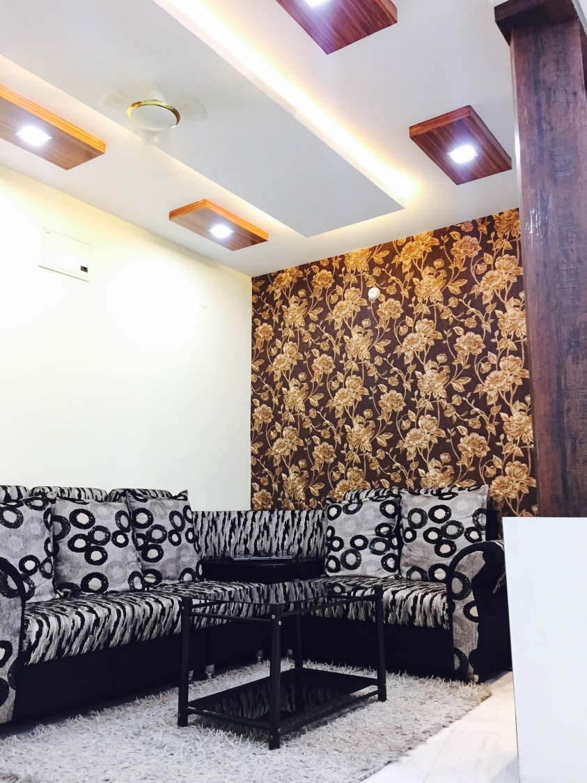 Living room decorated with white,grey and black print L shaped sofa,golden floral print wallpaper and decorative false ceiling with ceiling lights by Chaitanya Challa Living-room Eclectic   Interior Design Photos & Ideas