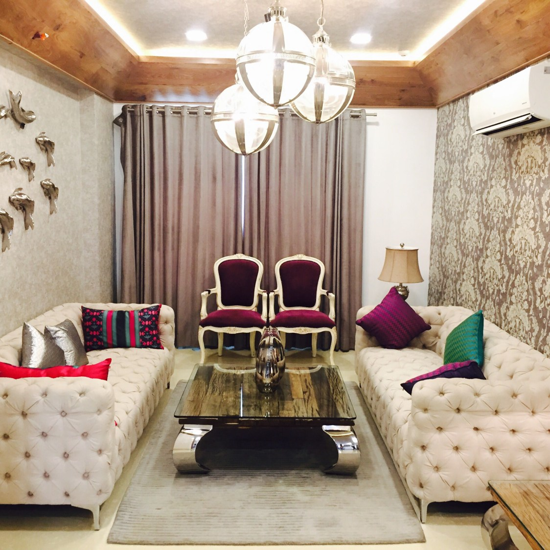 Life of the house:beige themed living room with tuxedo sofa and hanging decorative lights by Chaitanya Challa Living-room Eclectic | Interior Design Photos & Ideas
