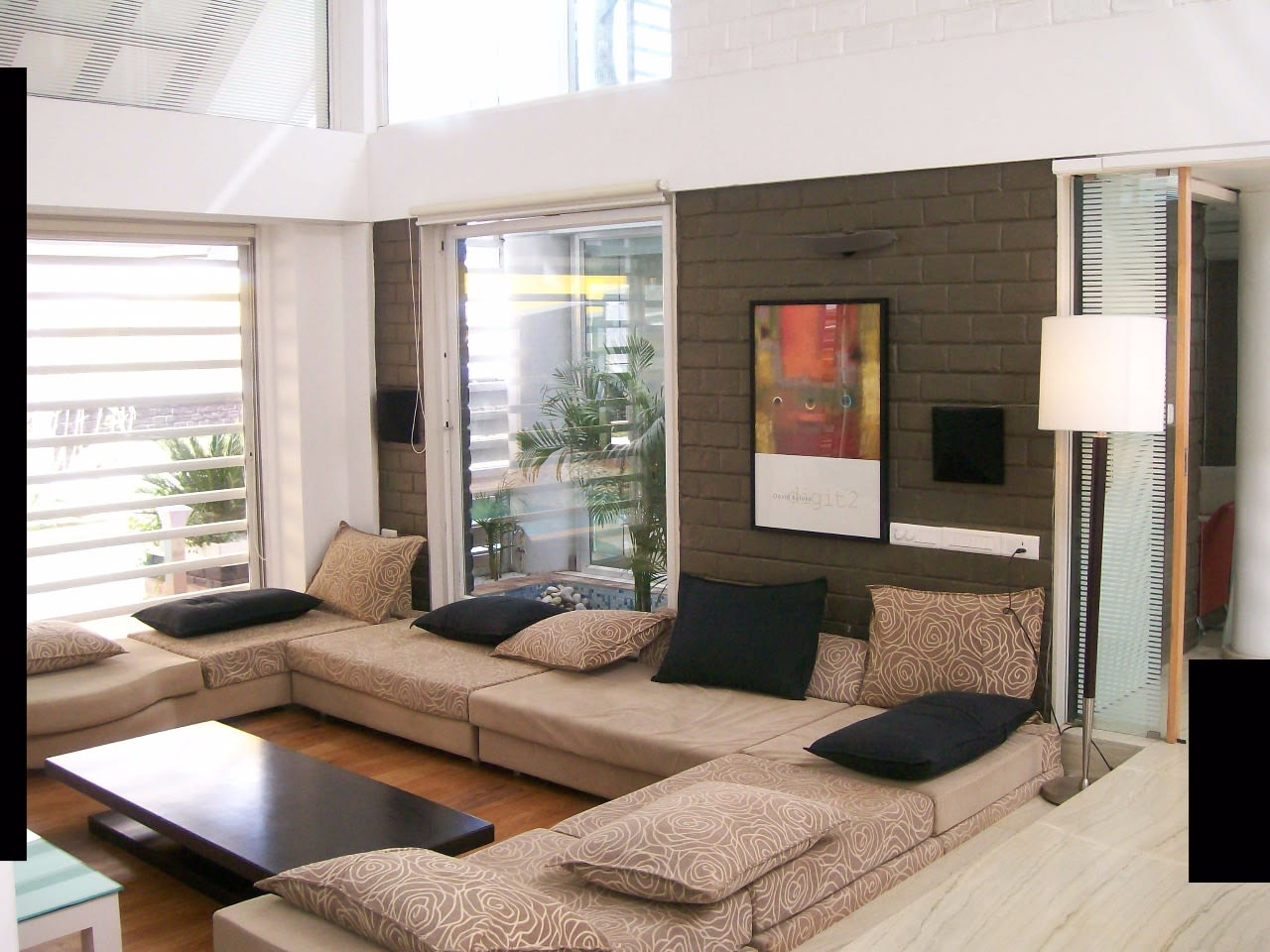 L shape sofa with wooden flooring  and brick wall design by Richa Jindal Living-room Modern | Interior Design Photos & Ideas