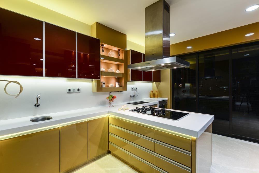 L shaped kitchen with white counter top and golden base and wall cabinets by Gocosy.com Modular-kitchen Modern | Interior Design Photos & Ideas
