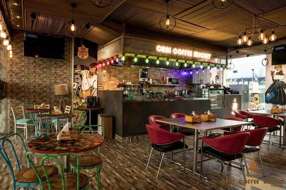 Design of a coffee shop with vibrant colored seats and wooden top tables lit by hanging lights by Vikas Swami Contemporary | Interior Design Photos & Ideas