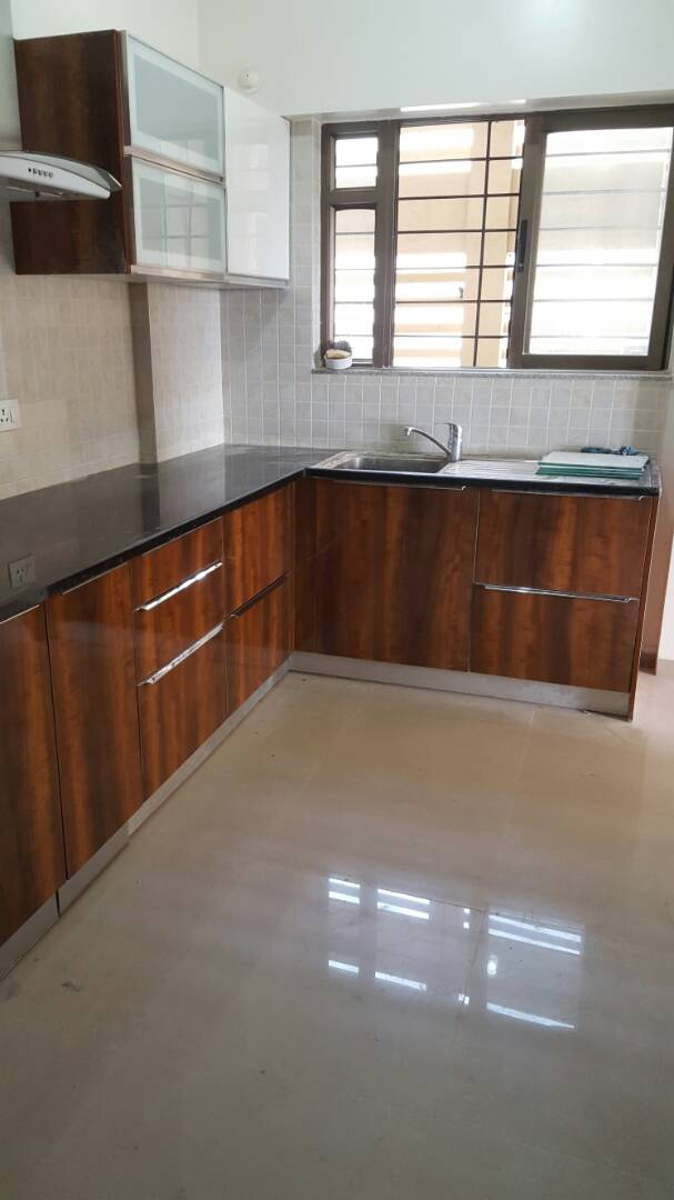 L Shaped Kitchen With Black Granite Counter Top And Wooden Base And Wall Cabinets By Simi Jajoo