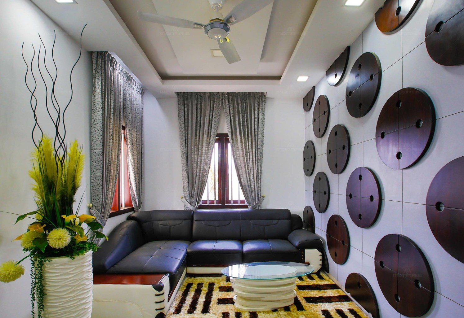 Compact Living Room with Black L Shaped Sitting Space and Circular Wall Art by Monnaie Architects Living-room Modern | Interior Design Photos & Ideas