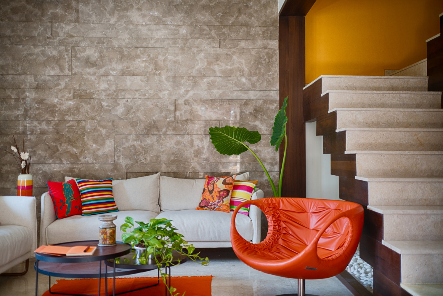 Beige patterned Wall with Orange Lounge Chair and Colorful Cushions Complimenting with White Sofa by Dhaval Patel Living-room Contemporary | Interior Design Photos & Ideas