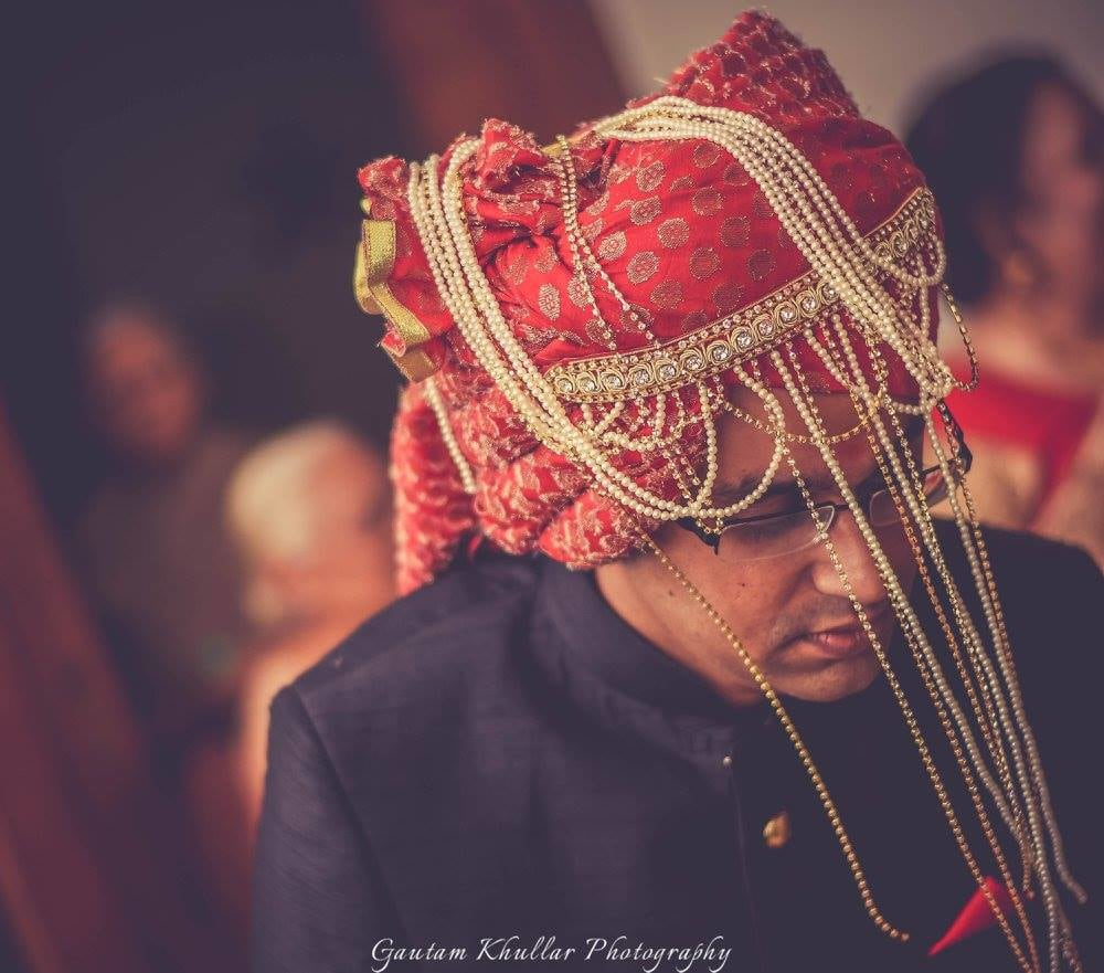 Candid Shot Of The Groom In A Red Safa With Golden Detailing And Pearls by Gautam Khullar Wedding-photography Groom-wear-and-accessories | Weddings Photos & Ideas