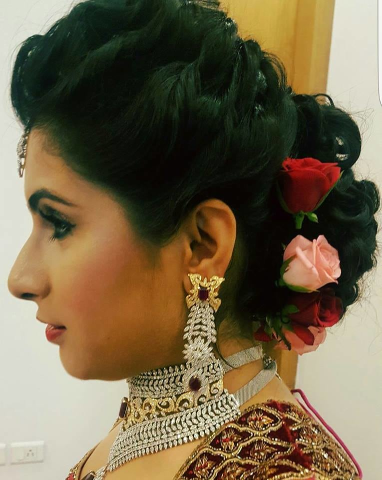 Flowers ornamenting her braided bun by Nishi Singh Bridal-makeup | Weddings Photos & Ideas