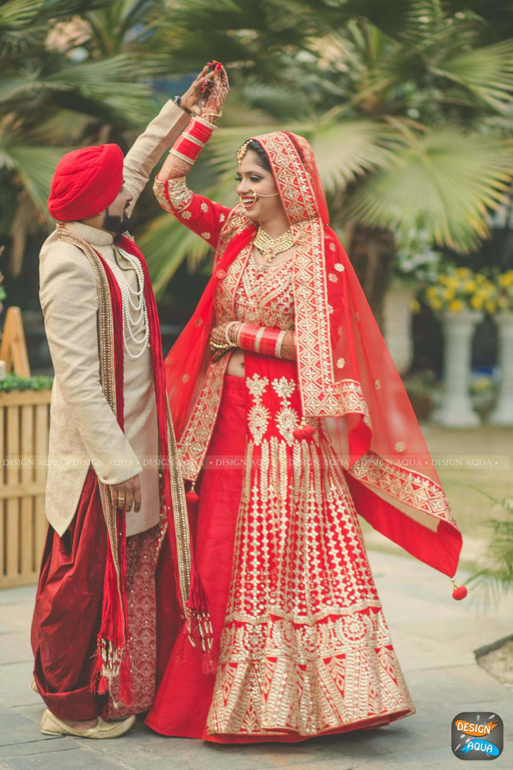 The Crimson Red Lehenga of the Bride Complimenting the Cream and Red Sherwani of the Groom by Priyanka Kamboj Wedding-photography Groom-wear-and-accessories Wedding-dresses | Weddings Photos & Ideas
