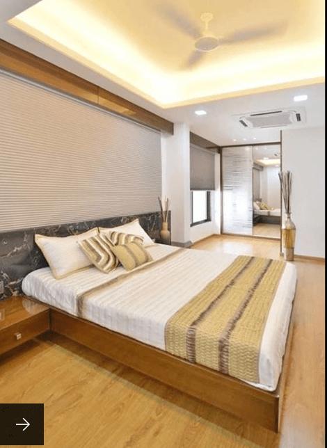 Bedroom With Hardwood Flooring And False Ceiling Illuminated By Led