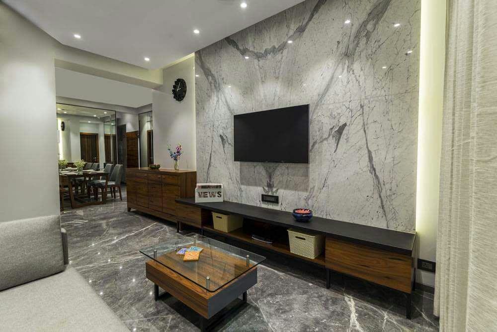 Glass Top Wooden Center Table And Marble Wall In Living Space by DD Jour Living-room Modern | Interior Design Photos & Ideas